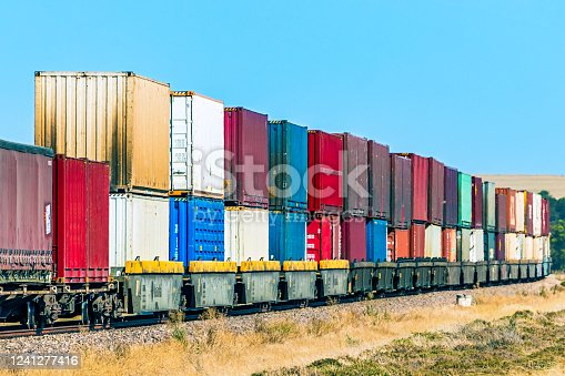 A colourful double stack container freight train carrying the equivalent load of dozens of big trucks (lorries) is transporting valuable merchandise to a distribution warehouse at its interstate destination. All logos and ID removed.