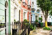 Houses painted in different pastel tones, in the corner of a street in Chelsea, London.