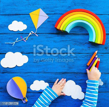Creative children's waldorf or montessori school concept. Paper crafts, colored pencils, wood rainbow with child hands on blue table. Kids art class, kindergarten, preschool background with copy space