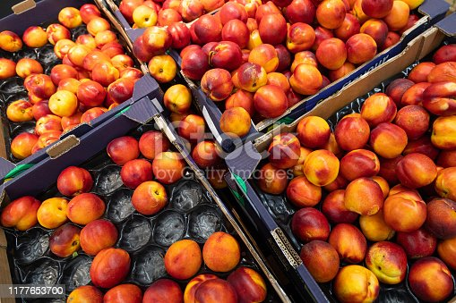 Colourful delicious nectarine in paper boxes at farmer's market of grocery store. For agruculture, food illustration backdrop. diagonal view