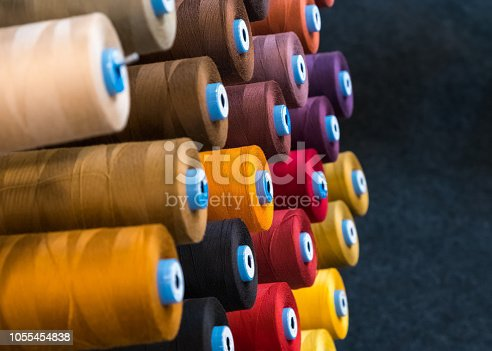 Colourful embroidery thread spool using in garment industry, row of multi coloured yarn rolls, sewing material selling in the market