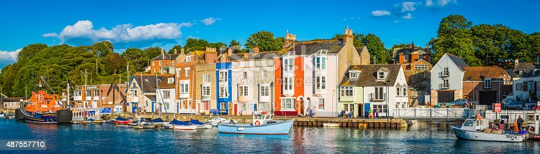 Weymouth, UK - July 30, 2015: Seaside tourists enjoying the warm summer sunshine on the quayside at Weymouth, Dorset, UK, in from of the brightly painted fishermen's cottages that line the old harbour. Composite panoramic image created from ten contemporaneous sequential photographs.