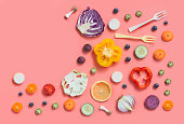 Colourful flat lay assorted sliced vegan food on pastel colour background. Healthy eating food text space image.