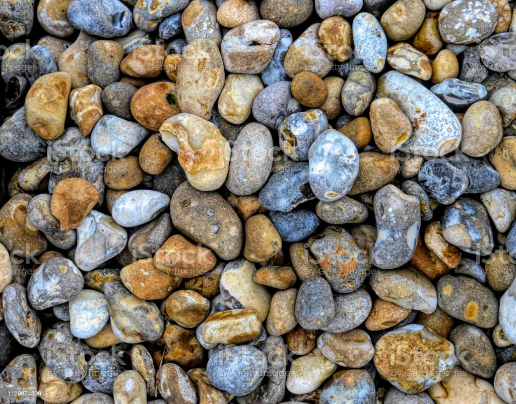 Colourful flint pebble background blue and orange stock photo