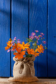 Colourful flowers in a burlap sack covered vase, in front of an old window shutter.