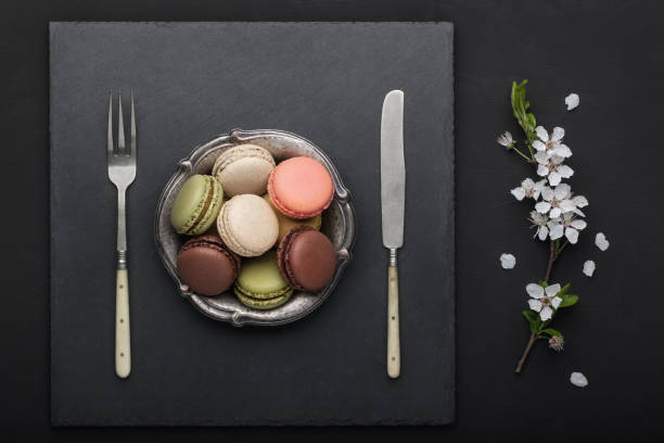 Colourful french macaroons in plate with spring blooming branch on black table. stock photo