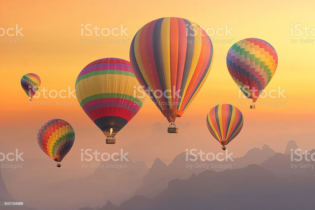 Colourful hot-air balloons flying over the mountain and traveler stock photo
