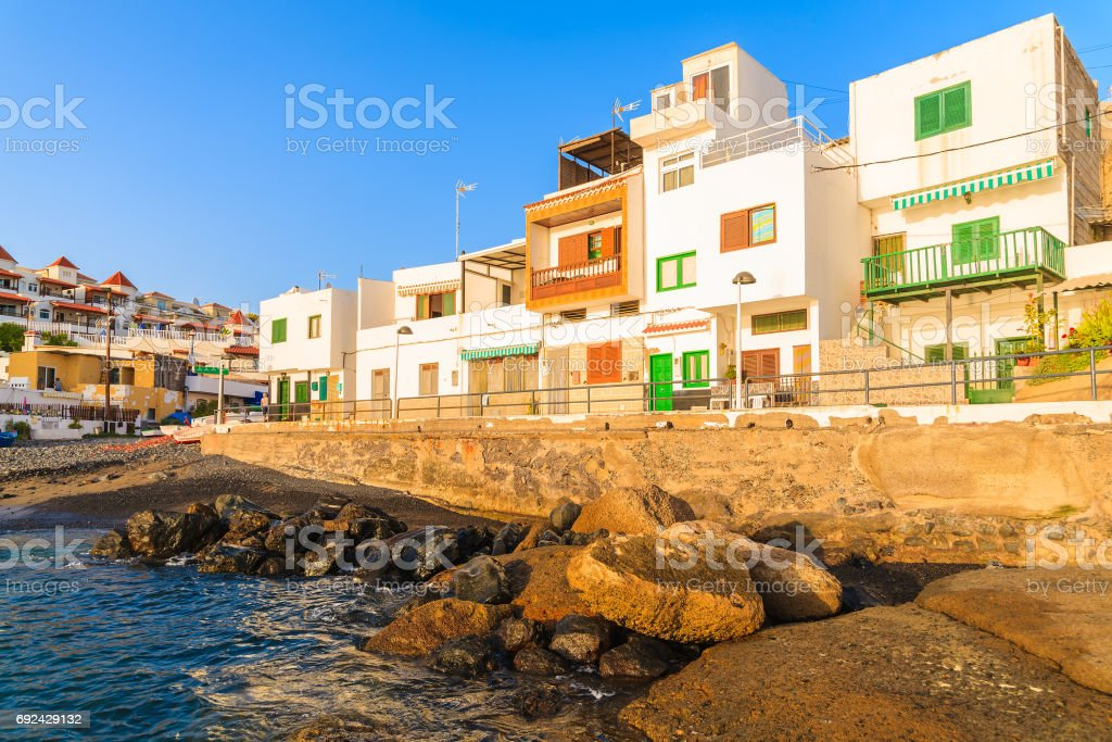 Colourful houses in La Caleta fishing village during sunset time on coast of Tenerife, Canary Islands, Spain stock photo