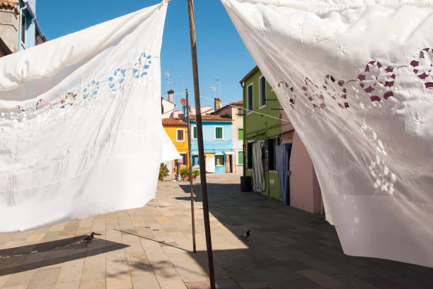 Colourful houses walls with hanging lace sheets in Burano, Venice, Italy - foto stock