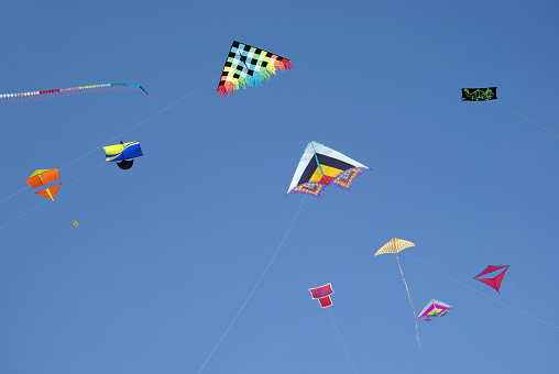 Colourful kites flying in blue sky