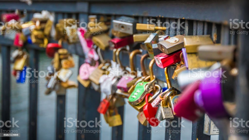 Colourful padlocks hanging from bridge with city in background stock photo