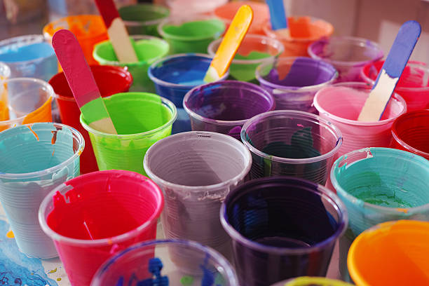 Colourful Paint Cups With Mixing Stick stock photo