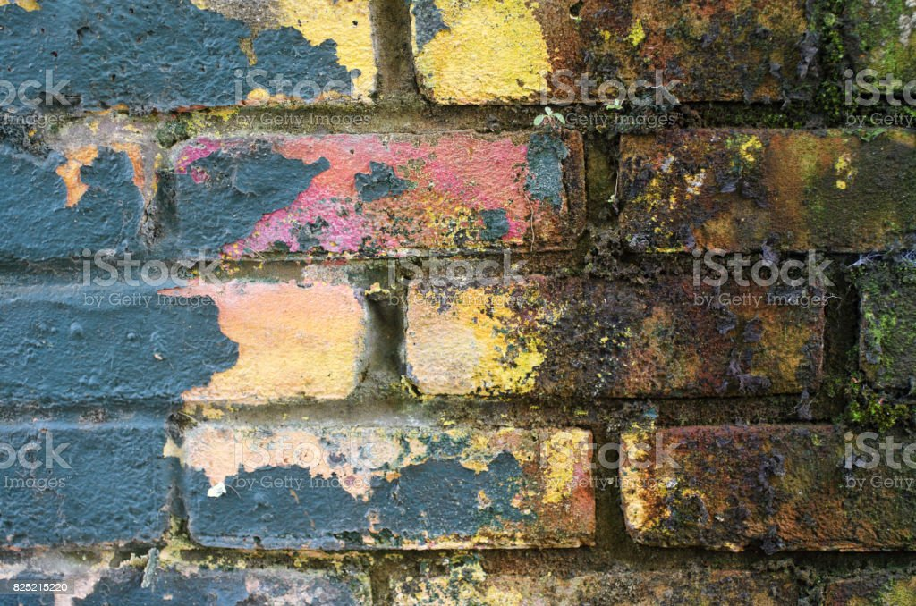 Colourful paint peeling from a damp brick wall pastel colours stock photo