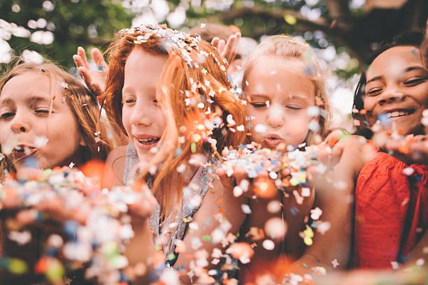 bunte papier konfetti, geschäumte in die kamera durch kinder - kinderparty spiele stock-fotos und bilder