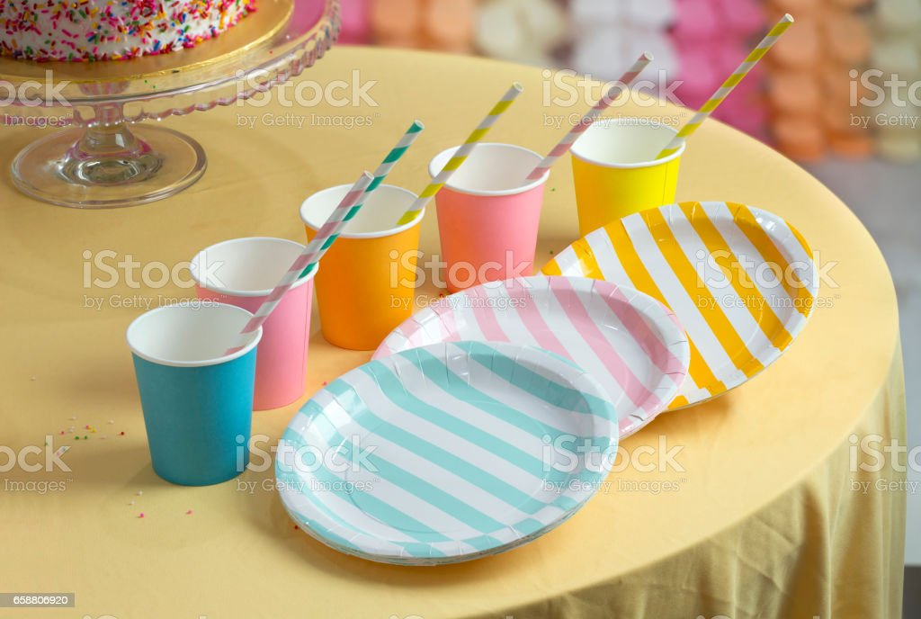 Colourful party paper cups and plates on table top. stock photo