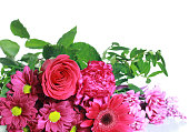 Colourful pink and purple coloured flowers on a white background. Flowers are lying down on a white wooden table .
