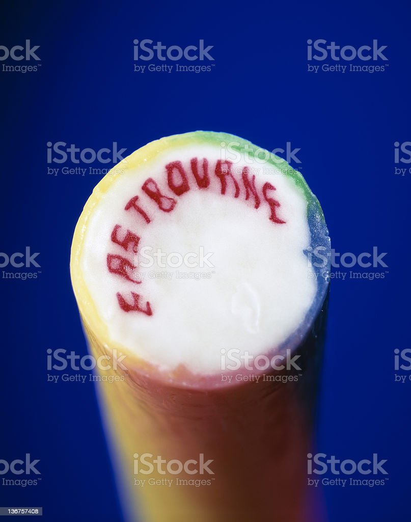 colourful stick of rock from eastbourne on vibrant blue background stock photo