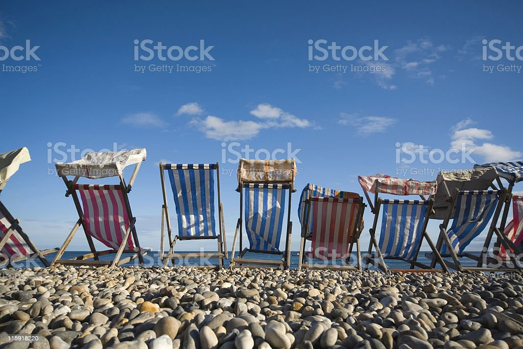 colourful striped deck chairs on a pebbled beach stock photo