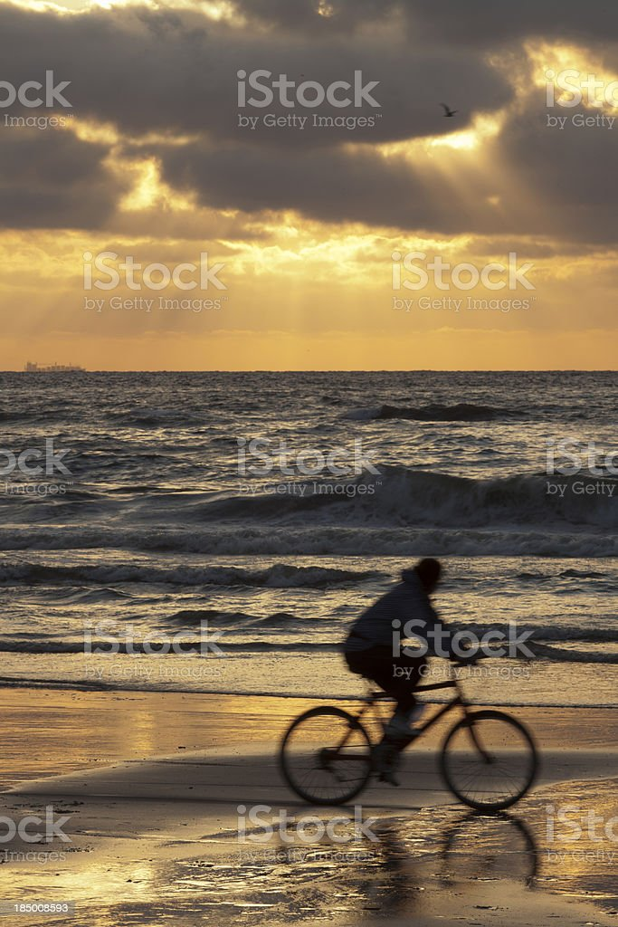colourful sunset over a mountain biker on the beach stock photo