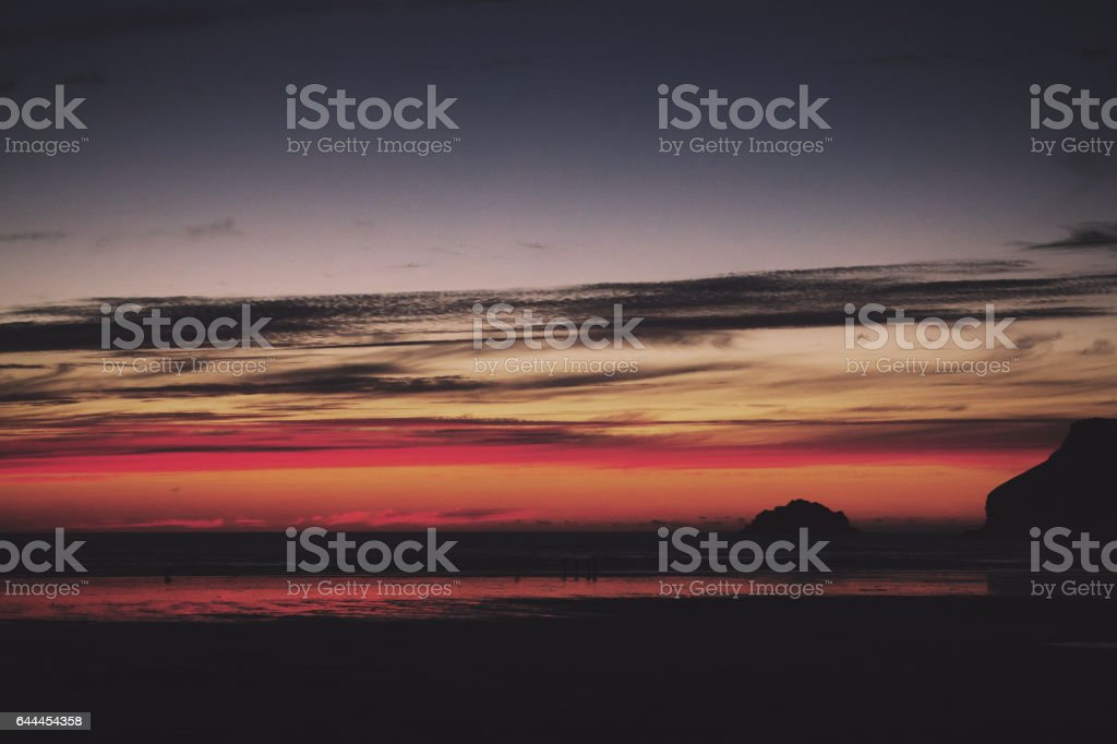 Colourful sunset over the beach at Polzeath Vintage Retro Filter. stock photo