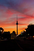 Berlin, Germany - 5 August 2018: Scene of the Berliner Fernsehturm (television tower) with colourful sunset in background and people driving on road beneath