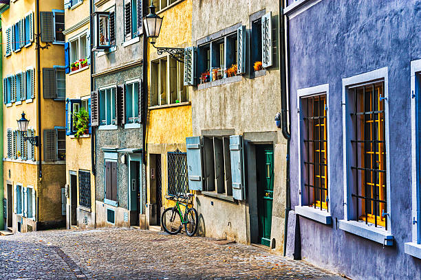Colourful Swiss City Architecture on the Streets of Zurich Traditional Swiss City Architecture on the Streets of Zurich. Realy nice and colourful view of city houses, with many different doors, windows and one bike how resting by the building. Zurich, Switzerland. zurich stock pictures, royalty-free photos & images
