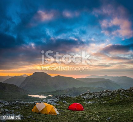 Colourful mountain tents pitched on an idyllic wild camp site high in the Lake District National Park, overlooked by the iconic peaks of Great Gable and Green Gable, Cumbria, UK. ProPhoto RGB profile for maximum color fidelity and gamut.