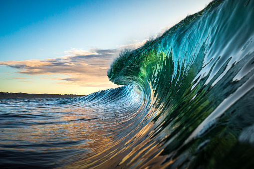 Colourful wave breaking in ocean over reef and rock