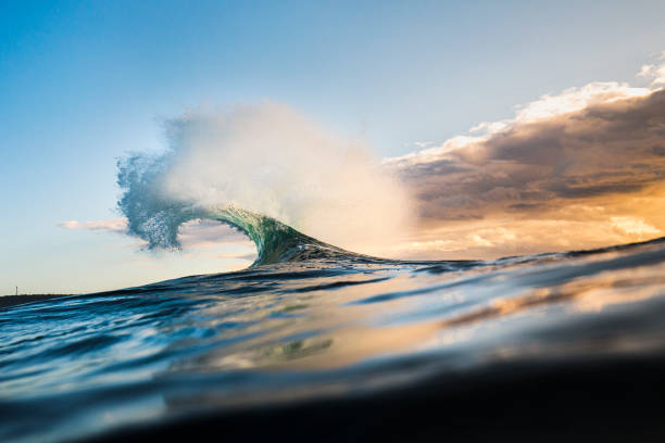 Colourful wave peaking into a flare with sunrise storm stock photo