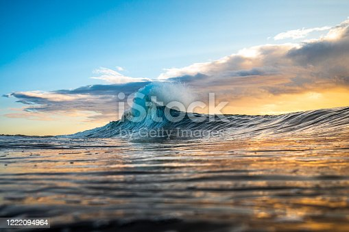 istock Colourful wave peaking into a flare with sunrise storm 1222094964