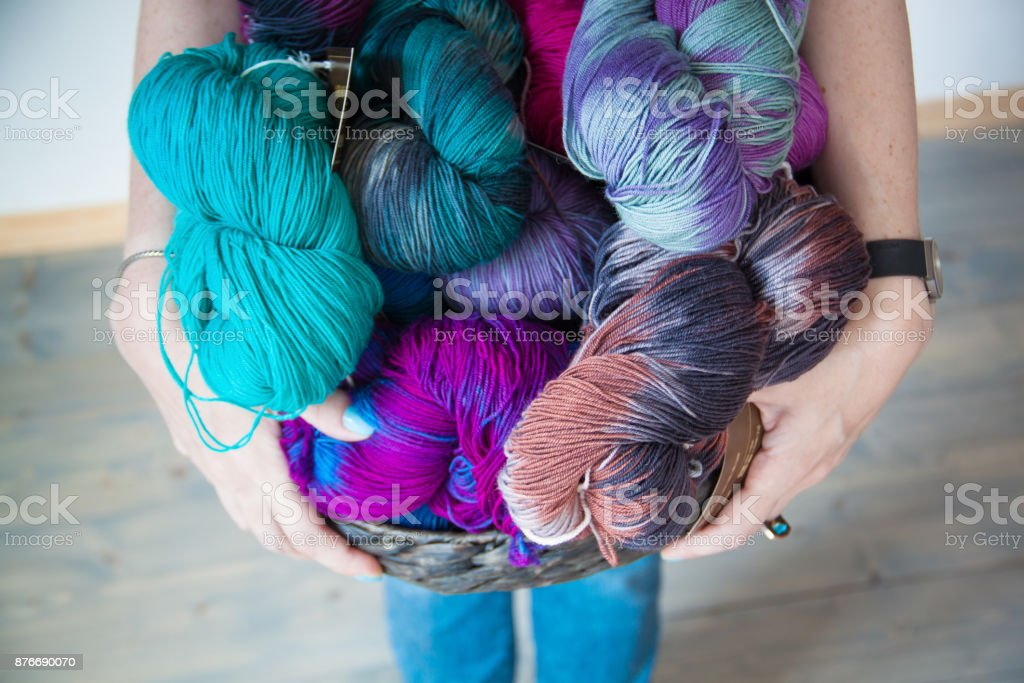 Colourful Yarn balls in the basket in hands stock photo