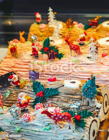 Colorful Christmas Swiss roll cake or buche de Noel with chocolate, chestnut cream and noel decorated with Santa Claus, rendeers, pine trees, red mushrooms and new year giftbox figure accessories in foreground on table. Celebration concept for Merry Christmas and New year.