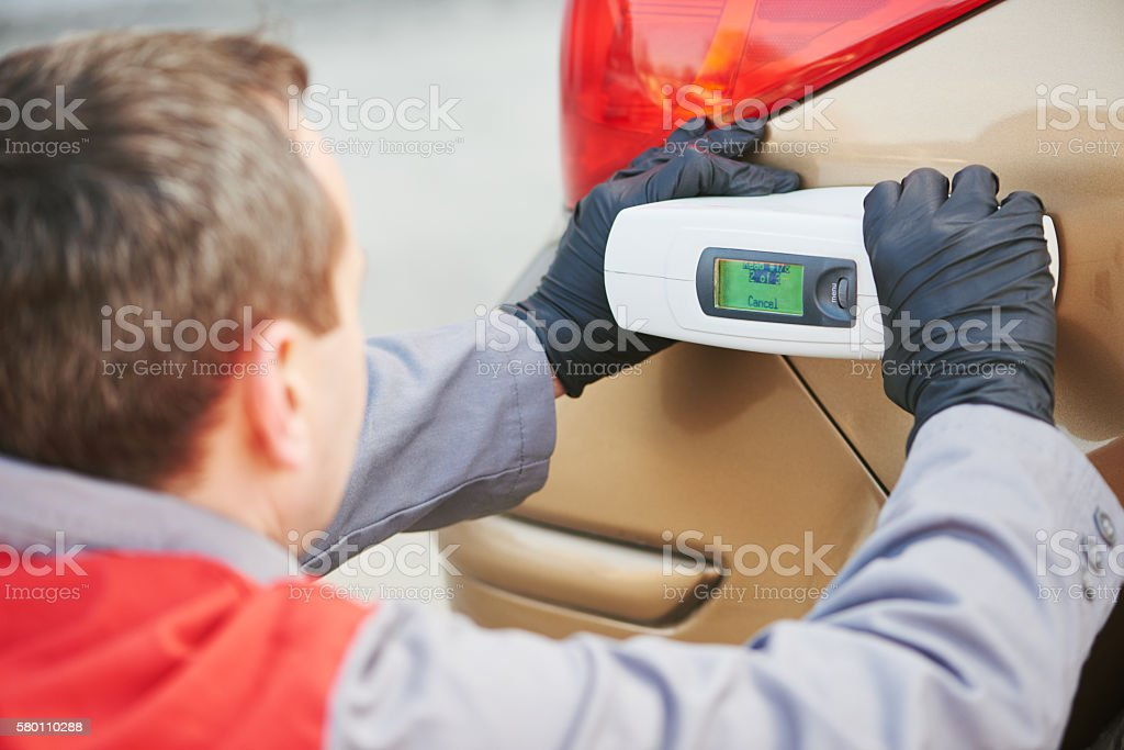 colourist man selecting color of car with paint matching scanner stock photo