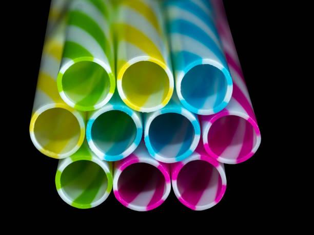 0607 Colourly gestreifte Kunststoff Trinken Strohhalme, schwarz u-Hintergrund – Foto