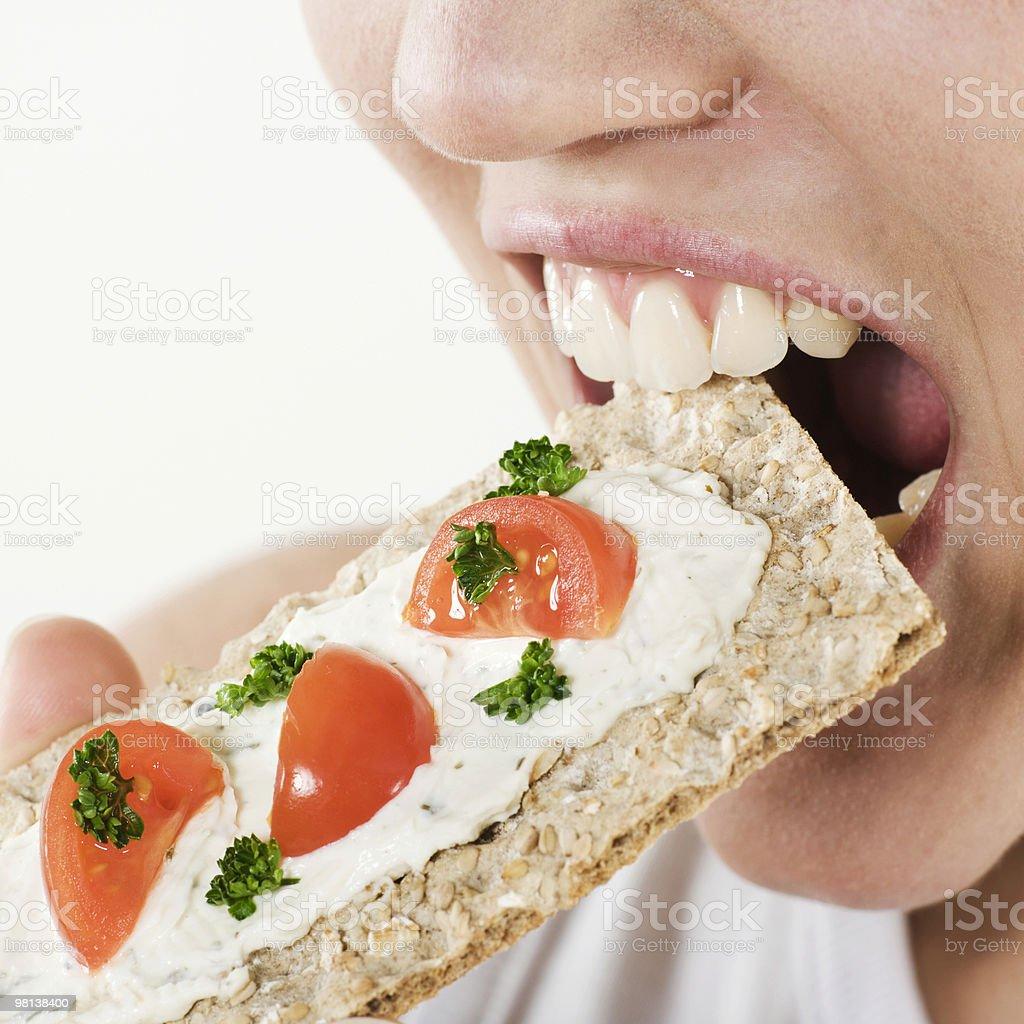 colse-up della bocca di donna mangiare rusk foto stock royalty-free