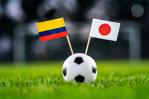 Columbia - Japan, Group H, Tuesday, 19. June, Football, World Cup, Russia 2018, National Flags on green grass, white football ball on ground.