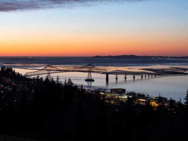 Columbia River Astoria–Megler Bridge at Astoria Oregon Evening Sunset An evening look at the bridge spanning the Columbia River from Oregon to Washington State. This is the Astoria–Megler Bridge. Crosses from Astoria Oregon to near Megler, Washington. Is unusually long at a little over 4 miles. oregon us state stock pictures, royalty-free photos & images