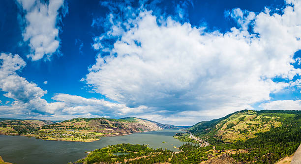 Columbia River Gorge panorama big sky over Oregon and Washington Sweeping panoramic vista over the Columbia River Gorge, from the Oregon shore, railway and highway across the wide Columbia River to the pretty town of Lyle and the Washington hills and forests beyond, Pacific Northwest, USA. ProPhoto RGB profile for maximum color fidelity and gamut. hood river valley stock pictures, royalty-free photos & images