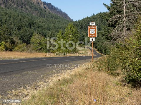 Cascade Locks, Oregon, USA - August 25, 2019:  A road sign for Oregon US 30 Historic Route is shown beside the road. This is next to Wyeth Trailhead used for the Historic Columbia River Highway State Trail. The new section of the trail opened in 2019 and can be accessed from I-84 or the historic US 30. This area offers spectacular views of the Columbia River with Oregon and Washington State scenery. This is part of the Columbia River Gorge.