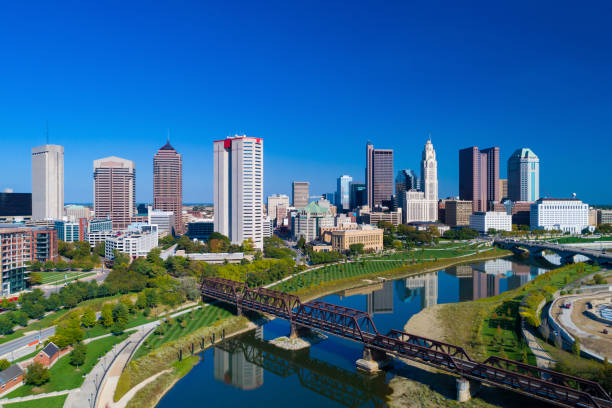 Columbus Skyline Aerial With River, Parks, and Railway Bridge Downtown Columbus skyline aerial with Alexander Park, Battelle Riverfront Park, Genoa Park, Scioto Park, Scioto River, and a railway bridge in the foreground. ohio stock pictures, royalty-free photos & images