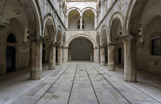 A Gothic looking chamber with columns, arches and a long entrance hallway.  Main focus on central hallway.