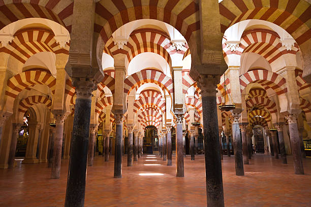 Columns forest located in Cordobas Mosque, Spain  Moorish architecture of the praying hall. The Mezquita is regarded as perhaps the most accomplished monument of the Umayyad Caliphate of Córdoba. After the Spanish Reconquista, it once again became a Roman Catholic church. cordoba mosque stock pictures, royalty-free photos & images