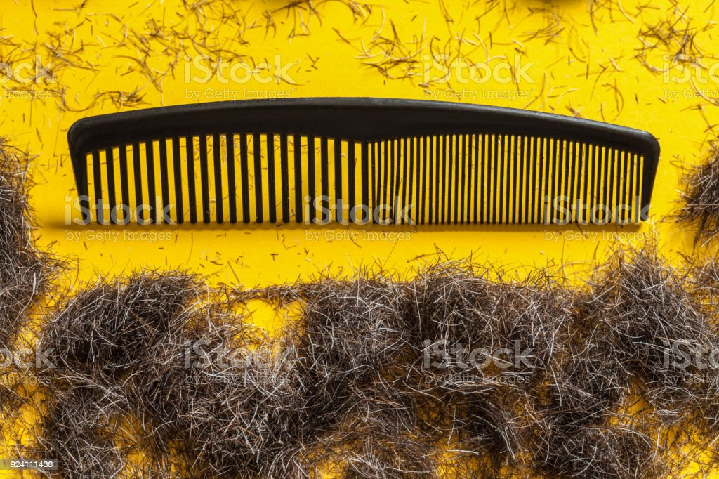 Comb and beard clippings on yellow background stock photo