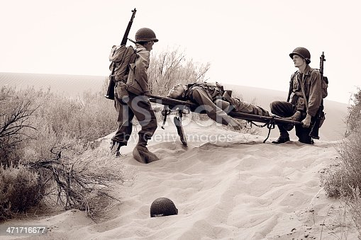 A World War 2 American army soldier in the desert is shot and wounded by the enemy. Two of his comrades carry him away on a stretcher. Part 3 of combat action sequence. Authentic WW2 army uniforms. Vintage black and white photojournalism style. More vintage military photos.