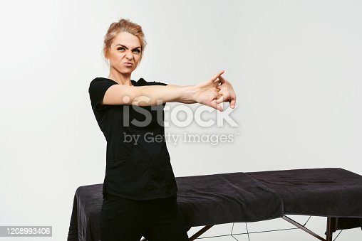 Combative mood! Young woman stretching her arms. Preparing to hard work