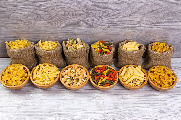 combinations of pasta in bags and  bowls on wooden background stock photo