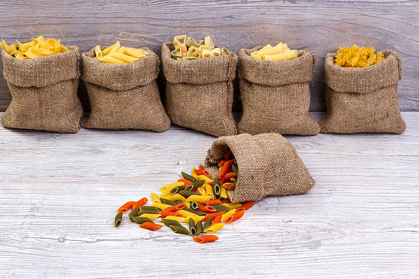combinations of pasta in  bags of burlap on wooden background stock photo