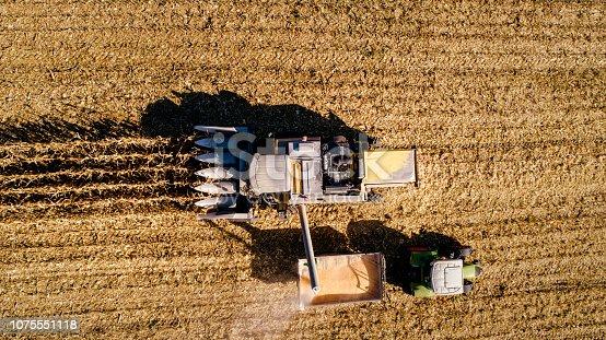 1072634078 istock photo Combine harvester unloading the corn into tractor trailer 1075551118