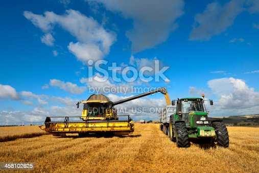 Rothenburg/Saale, Germany - July 12, 2012: Combine Harvester unloads Grain into Tractor Trailer under Cloudy Blue Sky