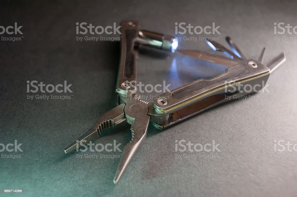 Combined pliers, multifunctional, with flashlight. Against the background of a gray texture stock photo